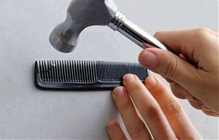 Человек вбивает молотком гвоздь, придерживая его расческой с мелкими зубчиками, чтобы не ударить себя по пальцам