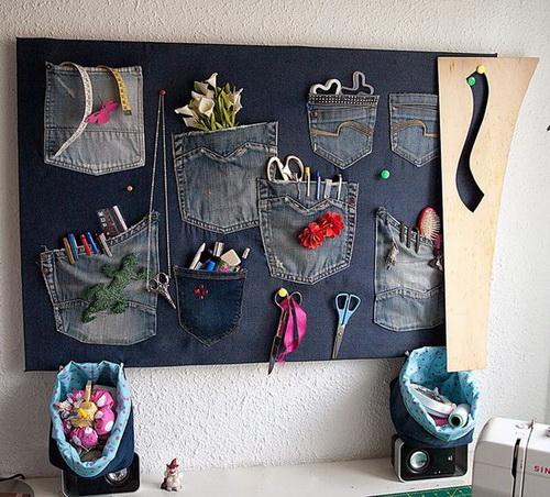 Доска на стене с нашитыми карманами, в которых хранятся инструменты для шитья
