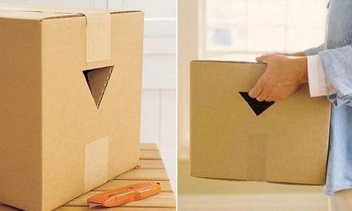 Человек держит картонную коробку с проделанными треугольными отверстиями для рук